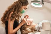 The Girl In The Salon Increases Eyelashes Client. The Process Of Eyelash Extension In A Beauty Salon poster
