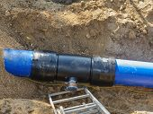 Repairing Process Of Underground Water Supply Pipeline. Blue Plastic Tubes In Trench Welded Together poster