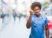 Afro american surgeon doctor man over isolated background angry and mad raising fist frustrated and  poster