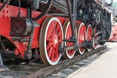 Red Large Iron Wheels Of An Old Vintage Locomotive On Railroad Close-up. Wheels Of A Locomotive. Lar poster