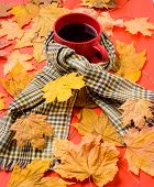 Mug Of Tea Surrounded By Scarf Red Background With Fallen Maple Leaves And Fir Cones. Mug Cozy Aroma poster