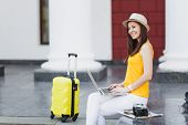 Smiling Traveler Tourist Woman In Casual Clothes, Hat With Suitcase Sit Using Work On Laptop Pc Comp poster