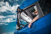 Heavy Load Cargo Delivery. Caucasian Truck Driver Inside Semi Tractor Cabin And The Blue Sky. Transp poster