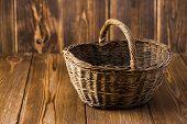 Wicker Basket Of Wicker On A Dark Wooden Table poster