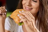 Closeup Of Tasty Croissant With Greens And Ham In Hands Of Pretty Girl. Smiling Woman Keeping Snack, poster