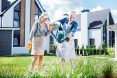 Bearded Grey-haired Man Holding Big Garden Sprinkler Watering Plants With Wife poster