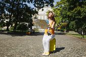 Happy Traveler Tourist Woman In Yellow Clothes, Hat Sitting On Suitcase Holding City Map Search Rout poster