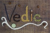 stock photo of fenugreek  - The word Vedic spelled out in a decorative way with spices and seeds used in the ayurveda diet and healing on a wooden countertop surface - JPG