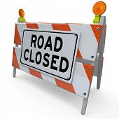 The word Road Closed on a barricade or barrier sign placed at a street or intersection to alert you