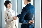 stock photo of unawares  - dangerous businesswoman holding knife behind her back while handshake - JPG