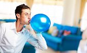 Portrait Of Young Man Blowing a�?� Balloon, Indoor