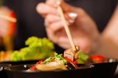 image of chopsticks  - Young people eating in a Thai restaurant - JPG