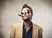 stock photo of delinquency  - Elegant young man smoking a cigar - JPG