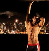 stock photo of muscle builder  - Sexy muscular young shirtless man at night with city lights and skyline in background with copy space - JPG