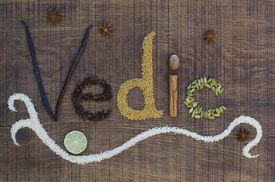 image of vedic  - The word Vedic spelled out in a decorative way with spices and seeds used in the ayurveda diet and healing on a wooden countertop surface - JPG