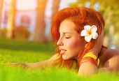 Profile of attractive woman with closed eyes dreaming outdoors, lying down on fresh green grass glad