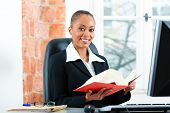 stock photo of diligent  - Young female lawyer working in her office with a typical law book and writing on the Computer - JPG