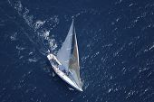 pic of watersports  - Top view of a sailboat in the peaceful blue ocean - JPG