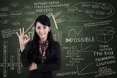 stock photo of gesture  - Beautiful businesswoman showing approval gesture in classroom - JPG