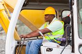 stock photo of heavy equipment operator  - african american man operates excavator on building site - JPG