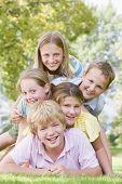 Постер, плакат: Пять молодых друзей свалили друг на друга на улице улыбается