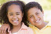 stock photo of brother sister  - Brother and sister outdoors smiling - JPG