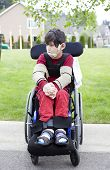 picture of biracial  - Disabled biracial six year old boy sitting in wheelchair on sidewalk - JPG