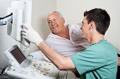 stock photo of ultrasound machine  - Male technician showing ultrasound machine - JPG