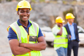 stock photo of ppe  - happy african industrial worker with arms folded - JPG