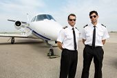 stock photo of jet  - Portrait of confident pilots standing in front of private jet - JPG