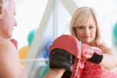 stock photo of boxing day  - Woman Boxing With Personal Trainer At Gym - JPG