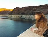 stock photo of dam  - A woman watches the sunset over Lake Mead from Hoover Dam - JPG