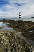 stock photo of anglesey  - Pebbled beach looking to small lighthouse and island - JPG