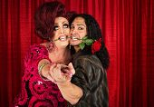 picture of drag-queen  - Embarrassed man with rose in mouth dancing with drag queen - JPG