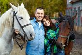 stock photo of stroll  - loving couple on a walk with horses - JPG