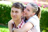 stock photo of love bite  - Cute couple in love looking happy while girlfriend is biting ear of boyfriend