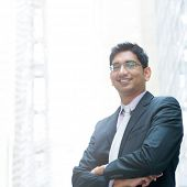 image of indian blue  - Portrait of a good looking smiling Indian businessman crossed arms standing at modern building - JPG