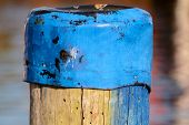 stock photo of bollard  - An old wooden bollard with an metal hat - JPG