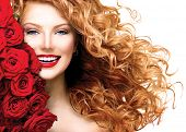 stock photo of hair blowing  - Beauty woman with long curly red hair and beautiful red roses hairstyle - JPG