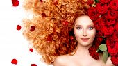 stock photo of hair blowing  - Beauty model girl with long curly red hair and beautiful red roses hairstyle - JPG