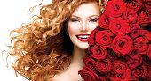 image of rose close up  - Beauty model girl with long curly red hair and beautiful red roses hairstyle - JPG