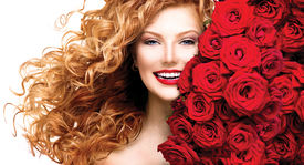 foto of hair blowing  - Beauty model girl with long curly red hair and beautiful red roses hairstyle - JPG