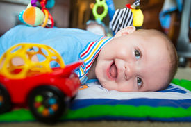 stock photo of playmate  - Happy and curious infant baby boy playing on activity mat - JPG