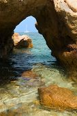 Yacht Through Stone Arch on Coast poster