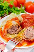 Постер, плакат: Cabbage stuffed with fork in plate on board