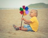 picture of laughable  - Baby playing with toy windmill - JPG