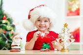 stock photo of santa baby  - kid girl in Santa hat holding Christmas cookies - JPG