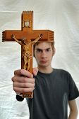 pic of fundamentalist  - Young man holds up a wooden crucifix of Jesus.