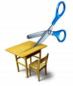 image of scissors  - School budget cuts crisis concept and education cutbacks symbol as an old class desk being cut by scissors - JPG