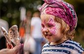 stock photo of masquerade  - Little girl having her face painted during local fair - JPG